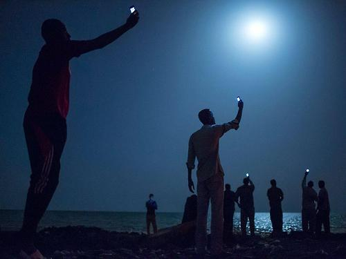 "Twitter / pourmecoffee: ""Djibouti migrants try to capture cheap cell signals from Somalia to call relatives"" (Photo: John Stanmeyer/@NatGeo) Update: original source at National Geographic, via Timo - Photo taken as part of the ""Out of Eden Walk"" series.Dennis Dimick, Executive Editor, Environment:""Standing as if waiting for signals from another world, these men on the Djibouti shores hope for a faint cellphone signal from neighboring Somalia. The power of this picture speaks to our enduring quest to explore—to connect with each other wherever we go—despite facing often daunting obstacles as we roam across the Earth. We are not alone. We are all connected, or try to be.""Elena Sheveiko, Photo Coordinator:""As it happens, I've worked with John Stanmeyer since his first ever story in National Geographic. And each story had an image that touched a hidden string in my soul. Years later, I still hear the sound. This picture from ""To Walk the World"" is one of them. It makes me want so much for everybody desperately trying to connect with others, to be heard and hear back from loved ones."""